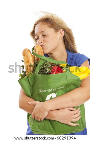 Humorous portrait of young woman with green grocery bag kissing food - stock photo