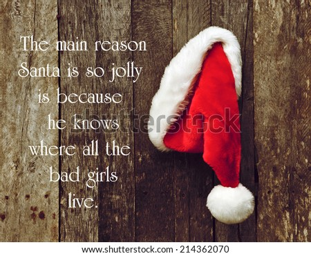 Humorous quote about Santa Clause by George Carlin, with Santa's hat hanging on a rustic wooden wall. - stock photo