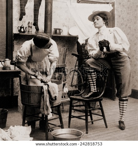 Humorous scene of life with 'the new woman.' Woman smoking and wearing knickers postures arrogantly as a man drudges over laundry. 1901.