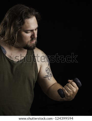 Humorous shot of a large man with tattoos lifting a very small weight - stock photo