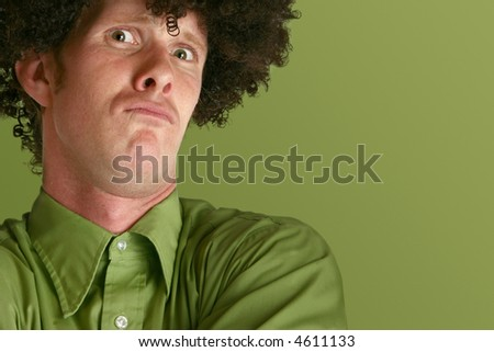 Humorous shot of thirty something man in black wig making crazy expression over green background.