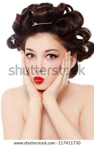 Humorous shot of young pretty girl with hair curles and surprised expression, over white background - stock photo