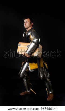 Humorous studio shot of young man dressed as medieval knight carrying away treasure chest (on black background) - stock photo