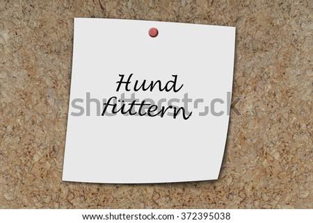Hund futtern (German feed dog) written on a memo pinned on a cork board - stock photo