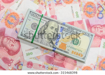 Hundred banknote of American dollars and Chinese currency yuan,Focus on American dollars - stock photo