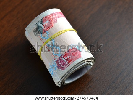 Hundred dirham notes rolled and tied with rubber band. - stock photo