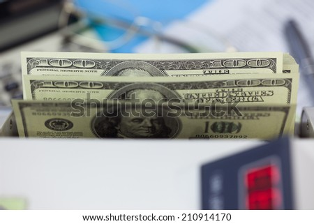 Hundred dollar banknotes in the counting machine - stock photo