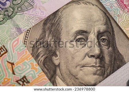 Hundred dollar bill surrounded by Chinese Yuan - stock photo