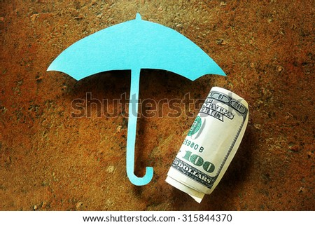 Hundred dollar bill under a paper umbrella -- financial security or retirement savings concept                                - stock photo