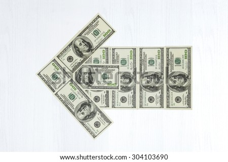 Hundred dollar bills arranged in the form of an arrow to the left - stock photo