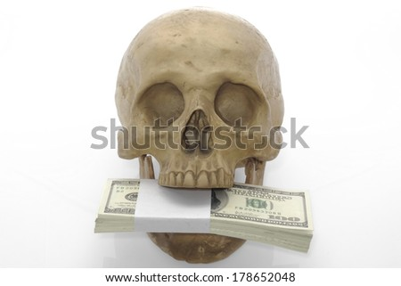 Hundred-dollar bills in skull mouth on white background. - stock photo
