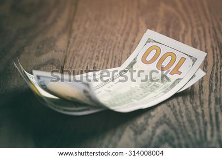 hundred dollar bills on wood table, vintage toned photo - stock photo