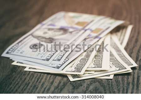 hundred dollar bills on wood table, vintage toned photo