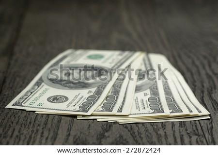 hundred dollar bills on wooden table - stock photo