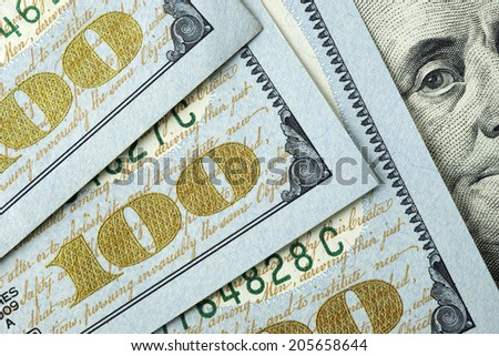 Hundred dollar bills with a close up of Benjamin Franklin's eyes. - stock photo