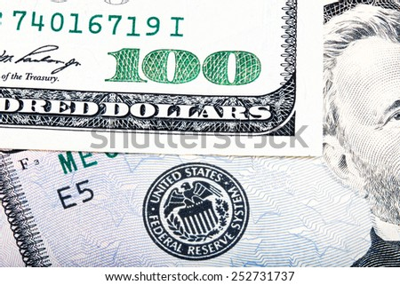 Hundred dollar near seal of Federal Reserve System. Stacked macro photo.