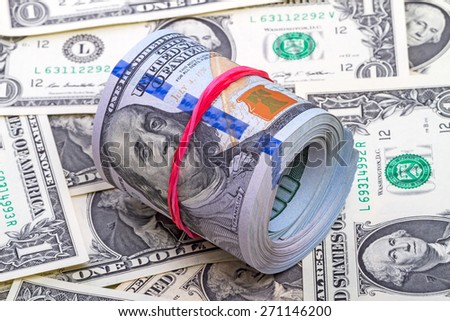 Hundred dollar roll up with red rubber on dollars background - stock photo