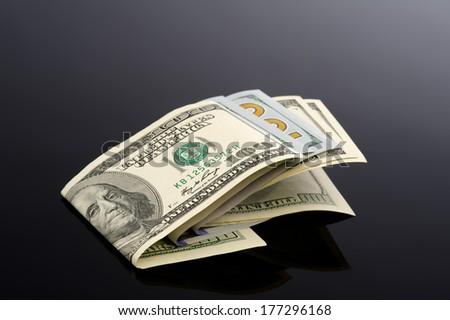 Hundred dollar Set laying on a black reflective background  - stock photo