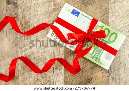 Hundred euro bill with red ribbon on wooden table - stock photo