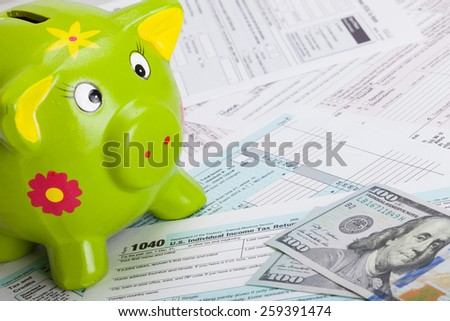 Hundred USA dollars banknote and piggy bank over US tax form - stock photo