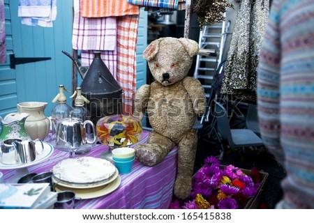 hundred years old and sad teddy bear on flea market - stock photo