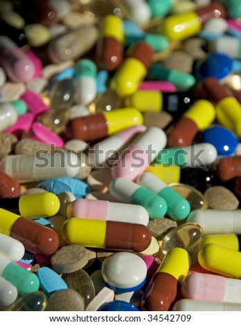 hundreds of assorted pills and capsules receding to BG.  Shallow DOF.  All trademarks removed.