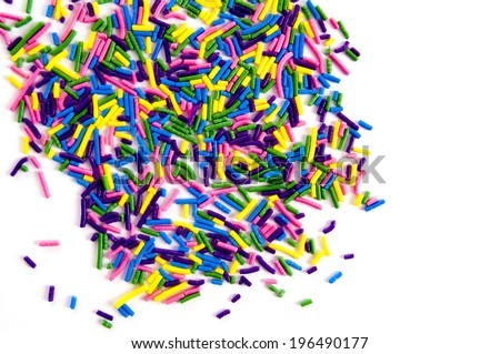 Hundreds of multicolored candy strands are scattered across a white surface.