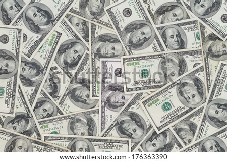 Hundreds of new Benjamin Franklin 100 dollar bills arranged randomly with the portrait facing uppermost in a closeup conceptual financial and monetary background