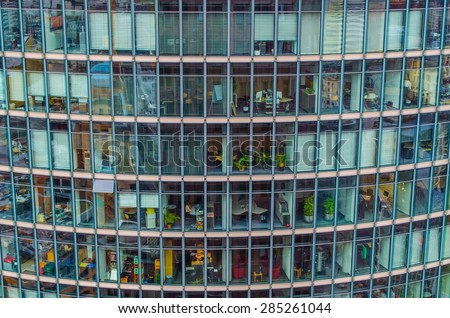 hundreds of people are working in many offices situated in steel and glass skyscraper in berlin. - stock photo