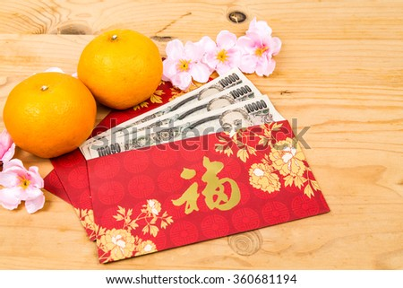 Hung Bao or red packet with Good Fortune Chinese character filled with Japanese Yen currency, displayed with mandarin oranges