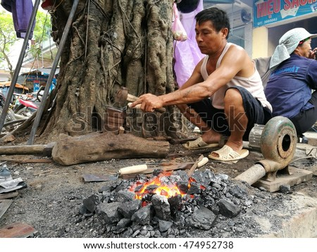 Hung Yen, Vietnam - Aug 11, 2016: Asian blacksmith forging agricultural tools outdoor on a monthly traditional flea market in Nom old village.