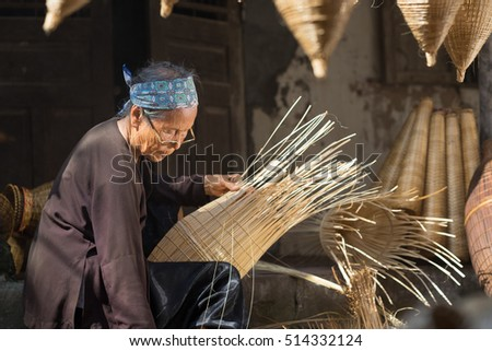 Hung Yen, Vietnam - July 9, 2016: Female craftsman making traditional bamboo fish trap at her old house in Thu Sy trade village