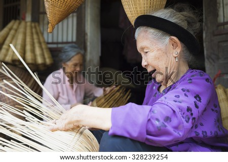 Hung Yen, Vietnam - July 26, 2015: Old woman weaves bamboo fish trap at Vietnamese traditional crafts village Thu Sy, Hung Yen province.