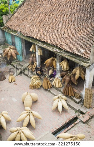 Hung Yen, Vietnam - July 26, 2015: Old women weaves bamboo fish trap at Vietnamese traditional crafts village Thu Sy, Hung Yen province.