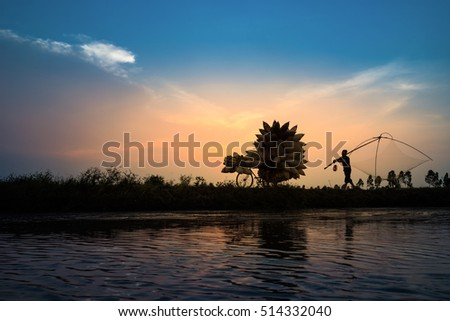 Hung Yen, Vietnam - July 9, 2016: Vietnamese rural countryside sunset scene with silhouette farmers carrying bamboo fish traps home in Thu Sy village