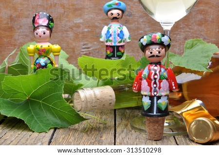 Hungarian decorative corkscrew, wine bottle and glass of wine on the wooden table with green twigs vine - stock photo