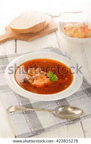 hungarian fish soup in a soup plate, salad and bread on a wooden board - stock photo