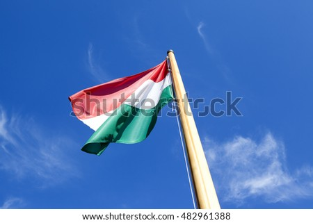 Hungarian flag flying against blue sky