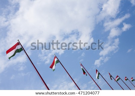 Hungarian National Flags blowing in the wind against the blue sky background