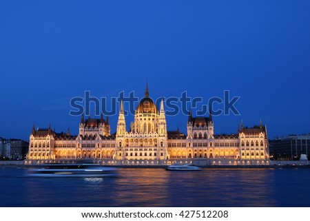 Hungarian Parliament Building along Danube River at night, with cruise ships in the foreground, Budapest. - stock photo