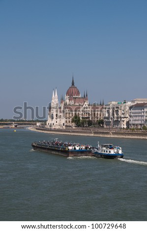 Hungarian Parliament in Budapest, while a boat is navigating on the Danube - stock photo