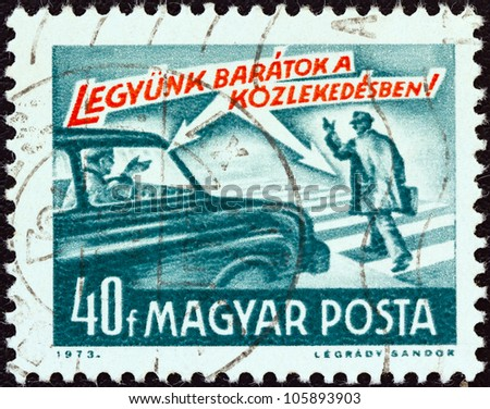 "HUNGARY - CIRCA 1973: A stamp printed in Hungary from the ""Road Safety"" issue shows car and pedestrian and ""let's be friends !"" inscription, circa 1973."