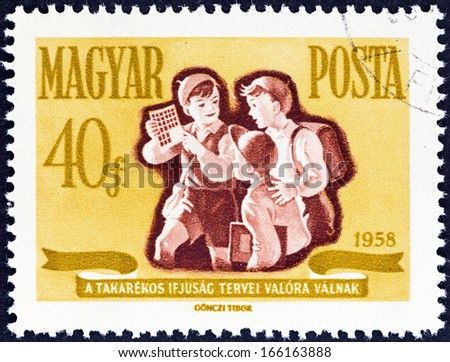 "HUNGARY - CIRCA 1958: A stamp printed in Hungary from the ""Savings Campaign "" issue shows schoolboys with savings stamps, circa 1958.  - stock photo"