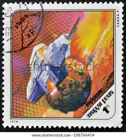 HUNGARY - CIRCA 1978: A stamp printed in Hungary shows a futuristic space ship around Phobos, the Martian moon, circa 1978. - stock photo
