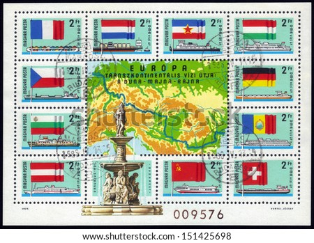 Hungary- CIRCA 1977: A stamp printed in Hungary, shows riverboats and the national flags of the countries through which passes European transcontinental waterway : Danube - Main - Rhine, circa 1977. - stock photo