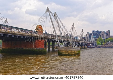 Hungerford Bridge in London in England. This bridge is a railway one and is also called Charing Cross Bridge. The street view with tourists. - stock photo