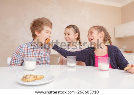 Hungry as a wolf. Children having fun together when a laughing girl puts a cookie into the mouth of boy at lunch - stock photo