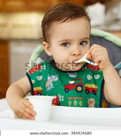 Hungry baby boy feeding himself dessert in a home setting.