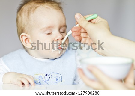 Hungry baby eating porridge. - stock photo