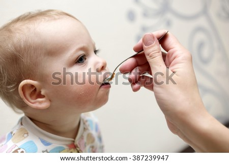 Hungry baby has dinner from the mother's hand